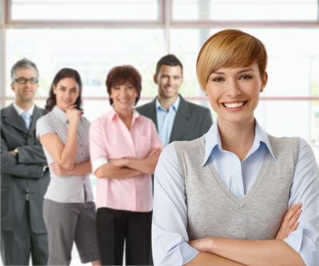 gingerish: Portrait of businesswoman and team of happy businesspeople. Stock Photo