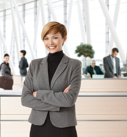 Attractive young happy businesswoman in office hallway. photo