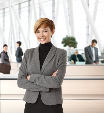 blazer: Attractive young happy businesswoman in office hallway. Stock Photo