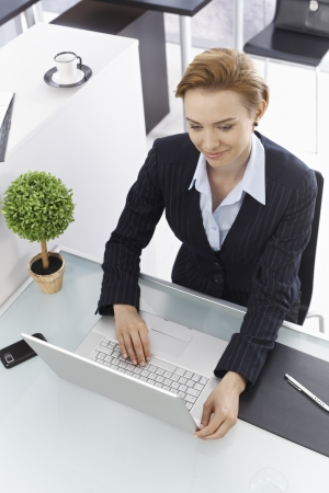gingerish: Businesswoman sitting at desk, working with laptop computer. Above view. Stock Photo