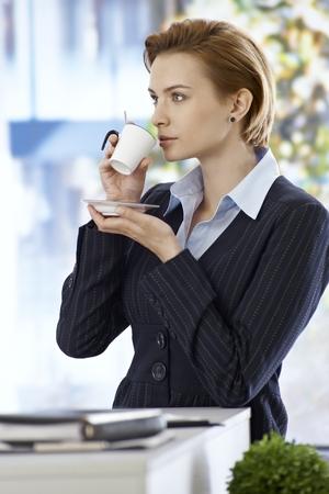 gingerish: Pretty businesswoman drinking coffee, looking away. Stock Photo