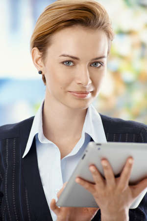 Beautiful young businesswoman using tablet computer, smiling, looking at camera. photo