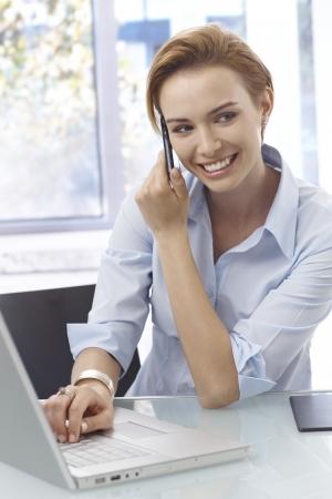 gingerish: Primer retrato de una mujer joven feliz hablando por tel�fono m�vil, utilizando equipo port�til.