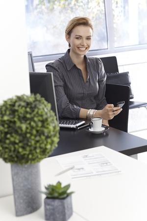 gingerish: Empresaria joven feliz que trabaja en la Oficina Verde, el uso del m�vil. Foto de archivo