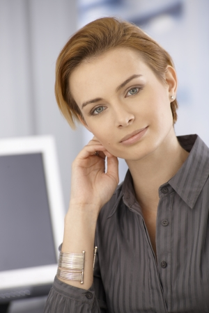 gingerish: Closeup portrait of attractive young businesswoman looking at camera, touching face.