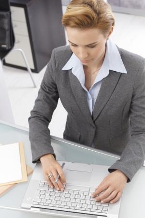 gingerish: Above view of elegant businesswoman sitting at desk, working on laptop computer, typing on keyboard. Stock Photo