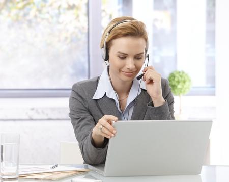 Young female dispatcher working, using laptop, wearing headphones, talking, smiling.