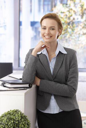 mujer sola: Hermosa joven empresaria sonriendo, mirando a c�mara, apoy�ndose en el mostrador.