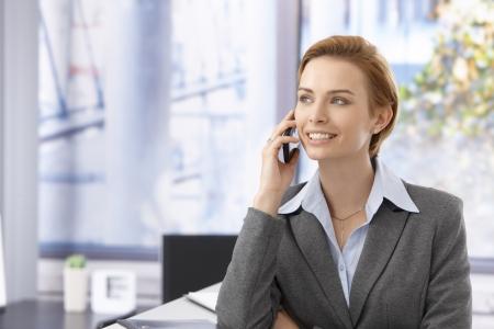 Attraktive junge Geschäftsfrau im Gespräch über Handy und schaute weg.