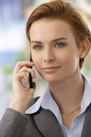 gingerish: Closeup portrait of attractive young businesswoman talking on mobilephone, smiling, looking away.