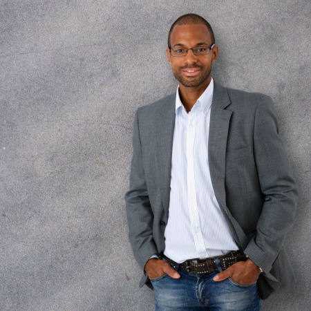 Portrait of confident and trendy black businessman leaning against gray concrete wall. photo