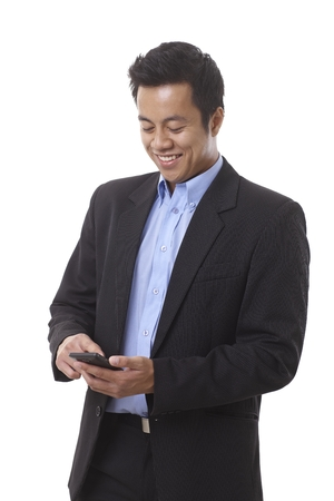 dialing: Young smiling Asian businessman dialing on mobilephone. Stock Photo