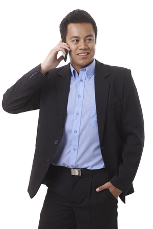 Businessman talking on mobilephone, looking away, standing with hand in pocket. photo