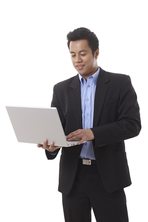 Businessman standing, holding laptop computer in hand, working. photo
