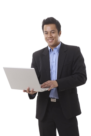 Happy Asian businessman holding laptop computer, working, looking at camera. photo