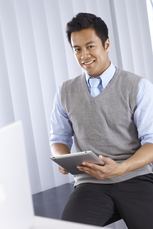 Happy young Asian businessman smiling, using tablet pc, looking at camera photo
