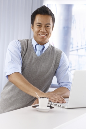 Happy young Asian businessman using laptop computer, smiling, looking at camera, leaning on counter photo
