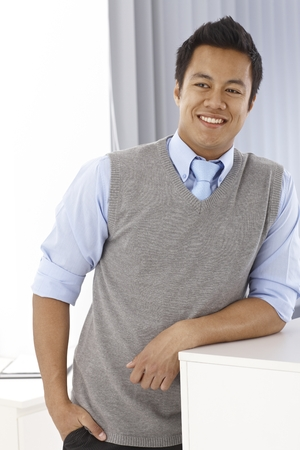 Portrait of happy young Asian man, smiling, looking away, leaning on counter photo