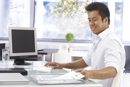 asian business man: Young Asian businessman working in bright office, sitting at desk