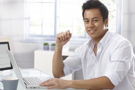 Portrait of happy young Asian businessman sitting at desk, working with laptop computer photo