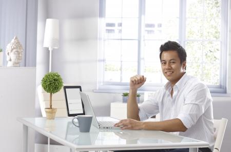 Hombre asiático joven que usa el ordenador portátil en casa, sentado a la mesa, sonriendo