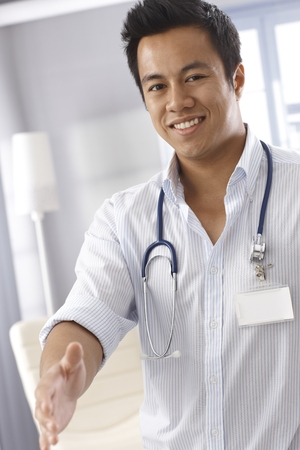 Young Asian male doctor giving hand for handshake, smiling, looking at camera photo