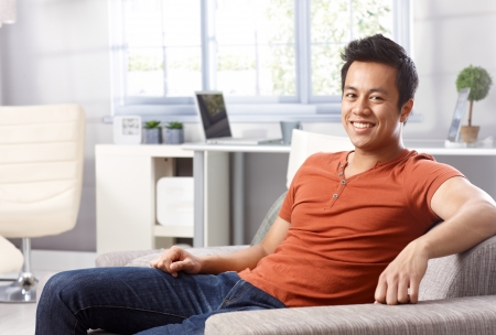 Handsome young Asian man sitting at home on sofa, smiling happy, looking at camera