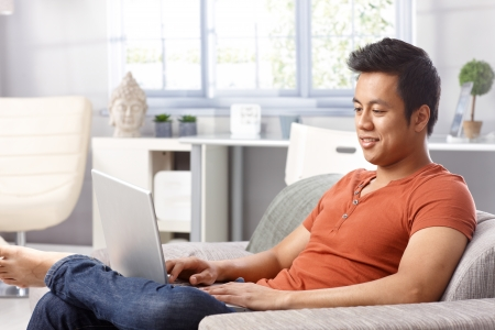 Young man using laptop computer at home, sitting on sofa