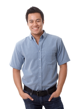 man standing alone: Casual young man in shirt and jeans smiling happy, standing with hands in pockets Stock Photo