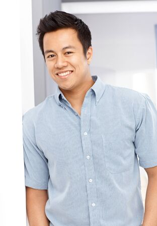 Portrait of happy young Asian man leaning against wall, looking at camera photo