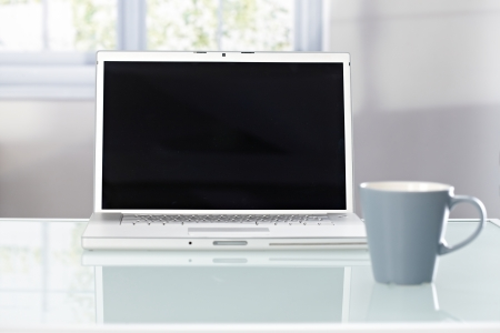 desk tidy: Closeup photo of open laptop with blank screen and tea mug on top of desk.