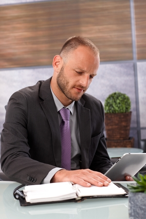 hesitating: Businessman sitting at desk in office, hesitating between tablet computer and personal organizer.