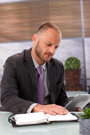dudando: Hombre de negocios sentado en el escritorio en la oficina, vacilando entre la computadora de la tableta y organizador personal.