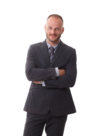 Happy businessman standing arms crossed over white background, smiling, looking at camera. photo