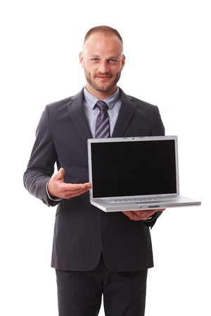 Businessman holding laptop with blank screen, smiling. photo
