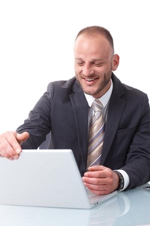 Happy businessman shutting down laptop computer, sitting at desk. photo