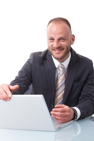 Happy businessman shutting down laptop computer, smiling, looking at camera. photo