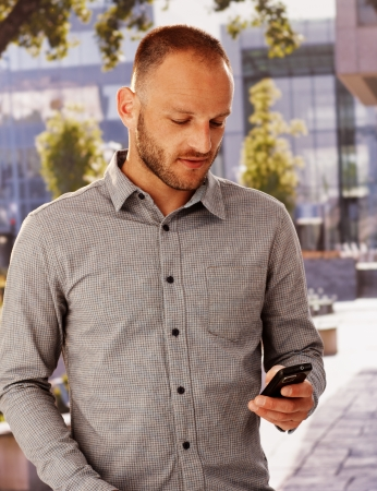 Casual young man using mobilephone outdoors, texting or dialing.