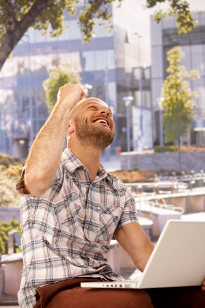 jitter: Young man shouting happy while sitting outdoors, using laptop computer, clenched fist. Stock Photo
