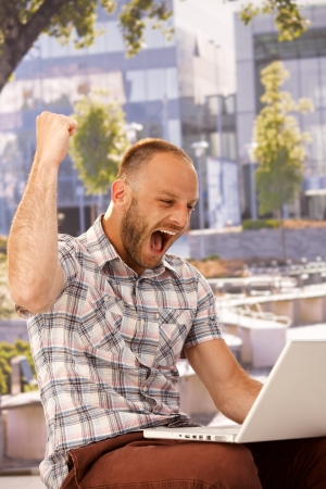 jitter: Young man using laptop, shouting happy with clenched fist.