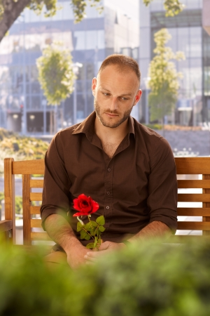 Disappointed man sitting on bench with red rose in hand. photo