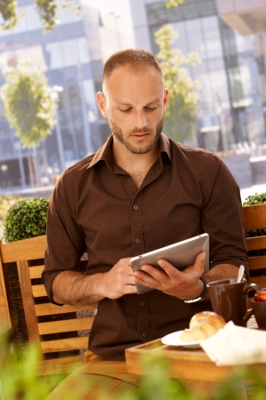 Young man using tablet computer outdoors, sitting on a bench, having breakfast in outdoor coffee. photo