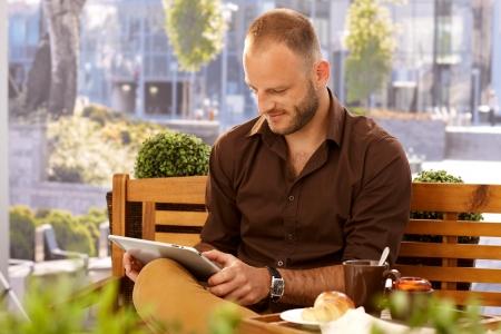 cafe internet: Casual hombre sentado en el café al aire libre en un banco, con tablet PC.