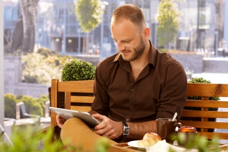 Casual man sitting in outdoor cafe on a bench, using tablet computer. photo