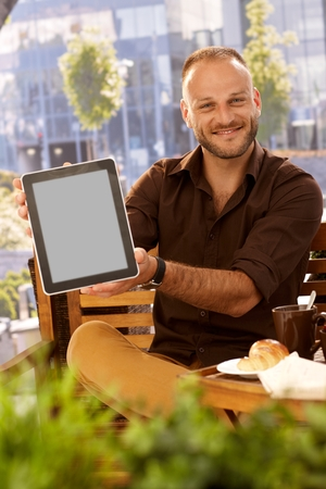 Happy man sitting outdoors, holding tablet computer with blank screen, smiling, looking at camera. photo