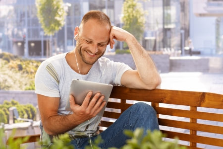 smiling man: Happy man reading e-book outdoors, smiling, using earbuds.