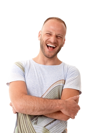 Portrait of laughing man in t-shirt standing arms crossed.