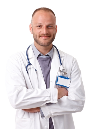 young male doctor: Portrait of confident young male doctor standing arms crossed, smiling, looking at camera.