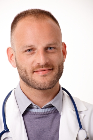 Closeup portrait of handsome young doctor, smiling, looking at camera. photo