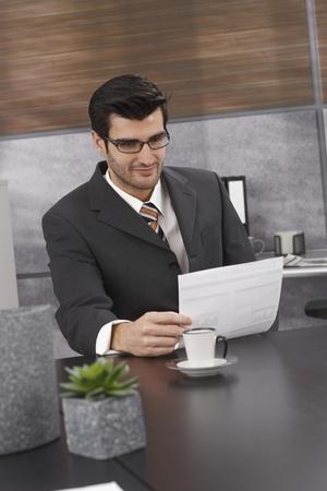 revisando documentos: Papeles de la lectura del hombre de negocios, sentado en el escritorio en la oficina.